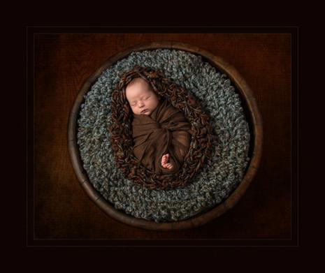 Newborn baby in a big wooden bowl
