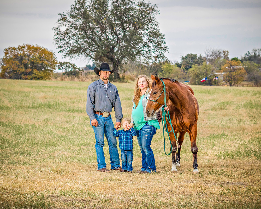 Portrait of a Smiling family on a farm with their horse