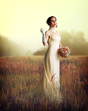 A beautiful bride at golden hour, in a field of grass.