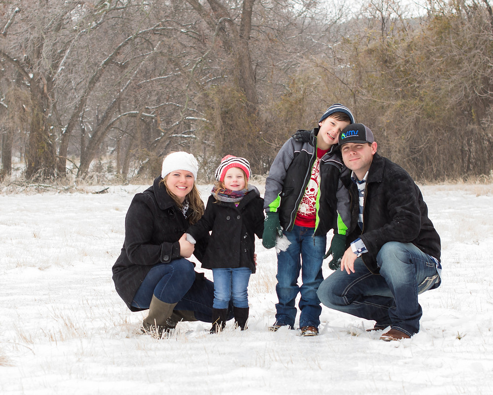 Portrait of a smiling family in a snowstorm
