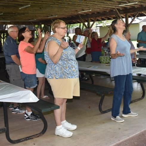 Worship time at church anniversary picnic