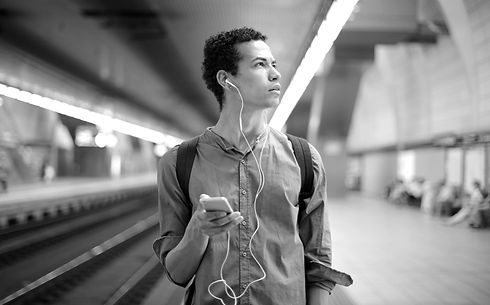young-ethnic-man-in-earbuds-listening-to
