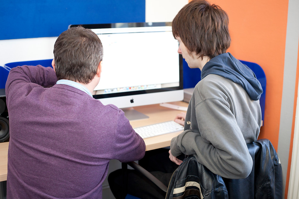 young person and tutor at computer