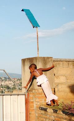 Je crois me souvenir que nous étions invités à un baptême, à Kigali. Toute la famille était réunie. Les adultes parlaient dans le jardin, les enfants jouaient autour d'eux. Et puis il y avait cette petite fille, qui regardait les gens passer dans la rue, par-dessus le portail. Comme en parfait équilibre au-dessus du monde extérieur…  As far as I can remember, we were at a baptism in Kigali. The whole family was gathered for the occasion. The adults were talking in the garden, the children were playing around them. And there was this little girl, who was looking over the gate, at the people passing in the street. Like in perfect balance over the outside world...  Kigali, Rwanda, décembre 2010.