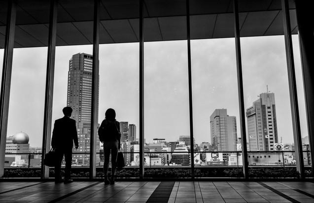 J'ai pris cette photo en haut d'un building du quartier de Shibuya. Je me demandais ce que ces deux personnes observaient, à quoi elles pensaient. Je les imaginais hypnotisées par le paysage extérieur, par l'effervescence humaine qui régnait dehors, par les néons des publicités géantes, par la vie à cent à l'heure qui défilait sous leurs yeux, une centaine de mètres plus bas. . I took this picture at the top of a building of the famous Shibuya's neighborhood. I was wondering what these two persons were observing, what they were thinking. I was imagining them hypnotized by the outdoor landscape, and all the human effervescence, the neon of the giant commercials, the hundred-and-one-hour life that unfolded before their eyes.  Shibuya, Tokyo, Japon, mai 2014.