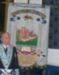 Lodge Banner Many of our Lodge furnishings were donated by the founders at the consecration meeting and in the earliest years. The generosity of the membership can still be seen in the many  outstanding and cherished artefacts with which the Lodge has been graced. One such item was the Lodge Banner. This magnificent and stunning Banner was generously donated by one of the early lodge stalwarts, W.Bro.Wally Davey, in 1956 when he was Senior Warden.  The Banner was hand embroidered in silk at the Royal School of Needlework in Kensington (now based at Hampton Court) and is truly a work of art. The Banner was dedicated at the  Installation meeting held in October 1956.