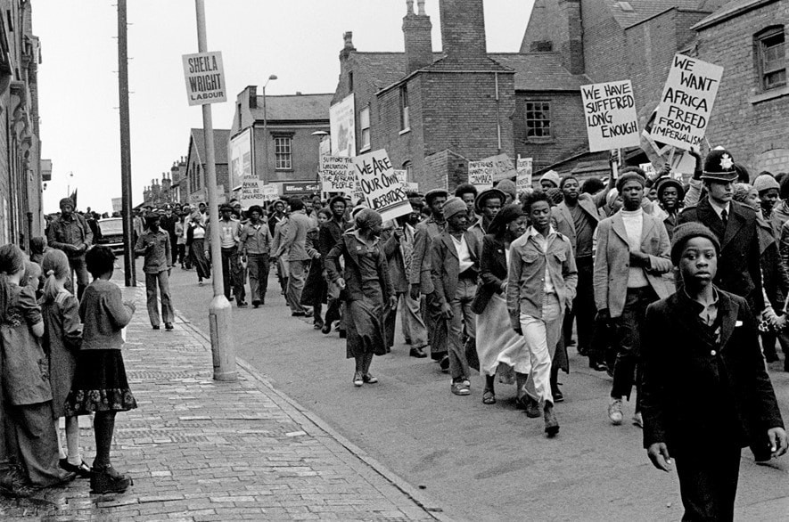 A black and white photo from 1977 of the The African Caribbean Self-Help Organisation (ACSHO) leading a march.