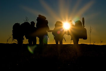Silhouettes of hikers walking in sunset