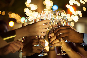 Group of friends cheers their wine glasses. You only see their hands & glasses with background blur