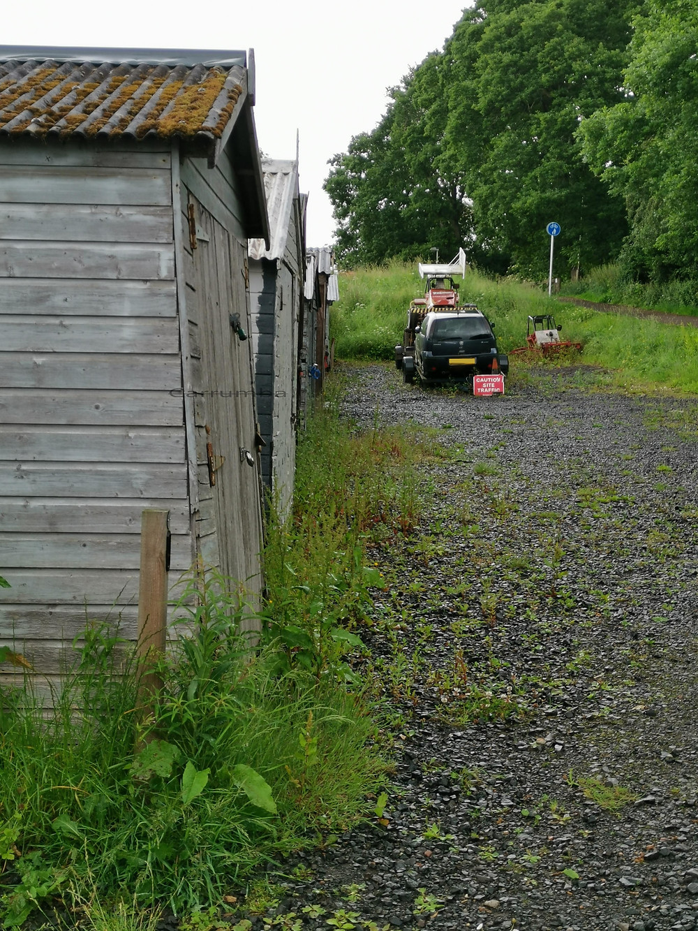 Five lockup garages in a row with corrugated iron rooves covered in moss. Abandoned stock car on trailer with black Vauxhall Corsa. Another stock car  frame in overgrown grass with path to right bordered by trees. Lockup garages surrounded by weeds.