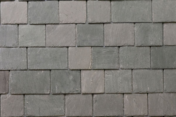 Slate wall cladding uses smaller sized slate tiles installed with zero headlap to reduce weght and cost.