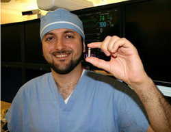 Dr. Ballany holding a tiny pacemaker the size of a vitamin pill