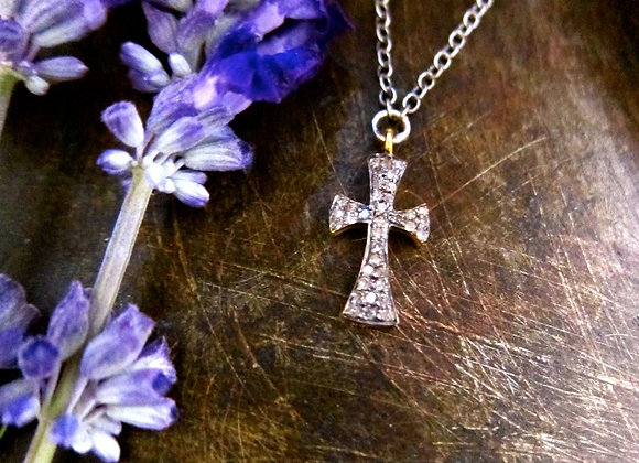 The Pave Diamond Cross in Sterling Silver next to flowers