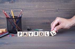 payroll. Wooden letters on dark backgrou