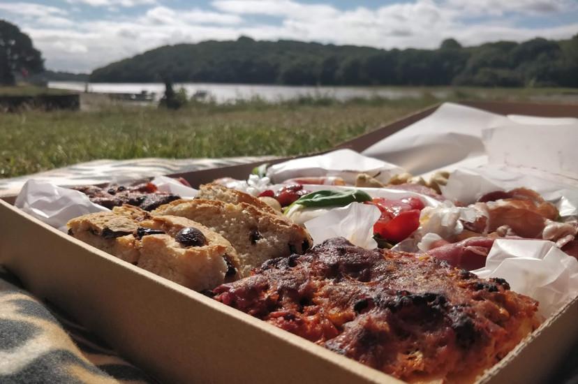 A gourmet picnic box enjoyed by the beach.
