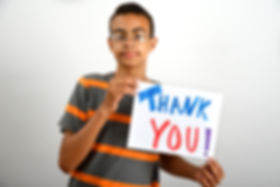 "A teenage boy holding a sign that reads ""Thank you!"" We are greatful for all of the supporters and donors that make HOW's work possible."