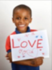 "Little boy with a sign that read ""Love."" The boy is part of HOW's Academic Coaching Program."