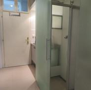Vorraum mit Kleinküch Dusche und WC im Glasverbau mit Schiebetüre