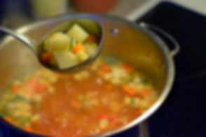 Ladle with vegetable soup. Cooking pot o