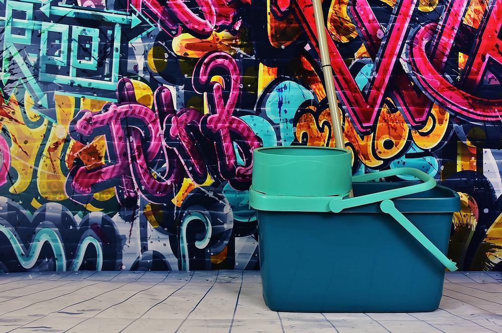 Zelený kbelík s mopem u zdi s grafity
