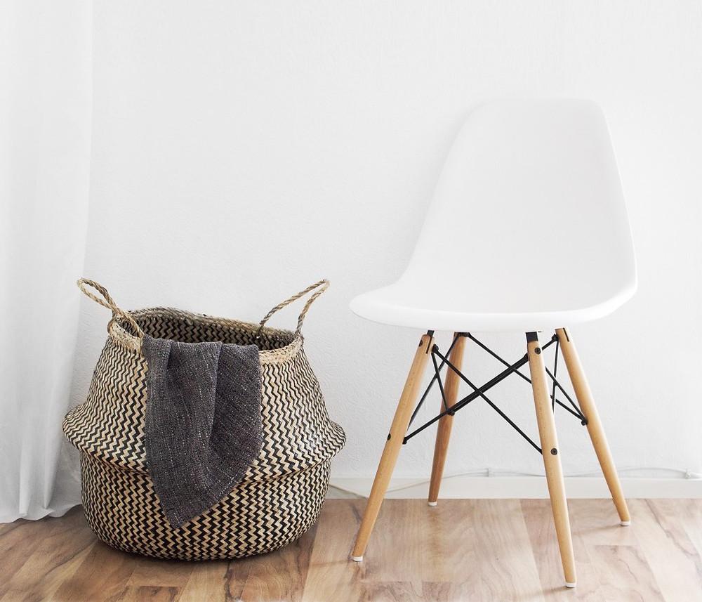 Proutěný koš na špinavé prádlo a moderní bílá židle