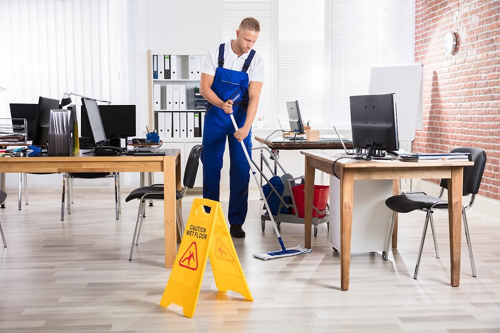 Profesionální úklidový pracovník při úklidu kanceláře.