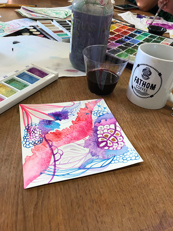 Image Description: An abstract watercolor of pinks, purples, and blues sits on a table beside watercolor paints, a glass of wine and a coffee mug that says Fathom Coffee on it.