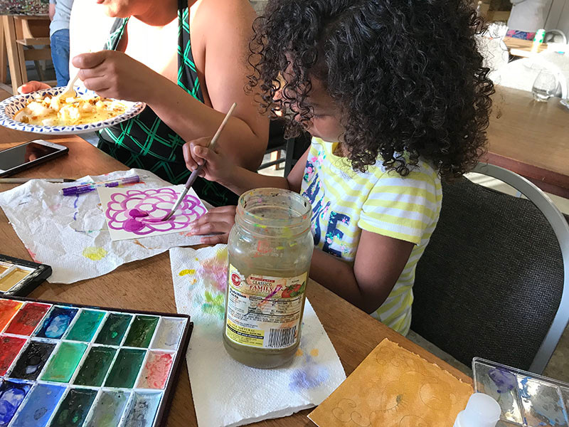 Image Description: A little girl with curly hair paints a flower with watercolors.
