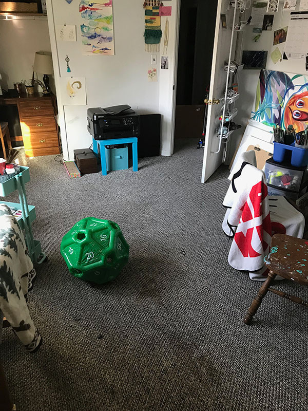 Image description: Image shows the empty, open floor of a room. There is a green ball shaped like a 20 sided die on the floor. There is a chair with a blanket to the right, and an open door leading out of the room in the background.