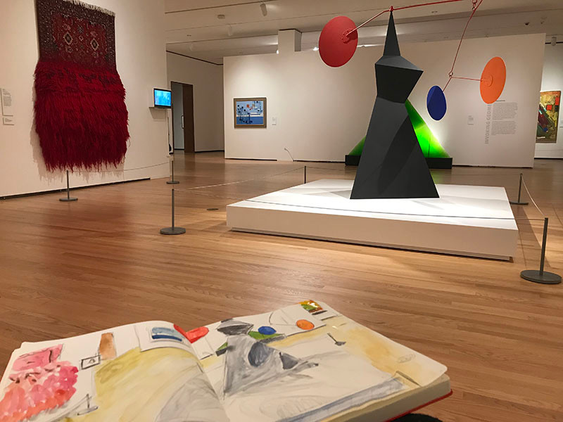 Image Description: In the foreground is a sketchbook depicting the scene in the larger part of the photo: an art gallery with a large rug hanging on the wall to the left, unraveling. There is a small painting to the left of center, and a large mobile sculpture in the center of the room. Behind it is a large triangular green sculpture.