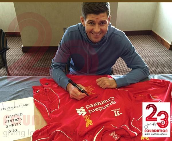 Steven Gerrard signerer drakt som selges til inntekt for 23 Foundation. Foto: jamiecarragher23.com