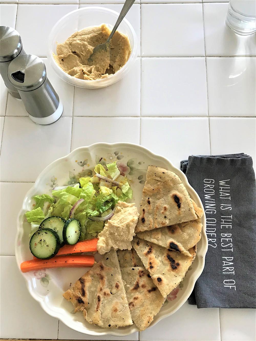 salad, hummus, carrots, and cucumbers