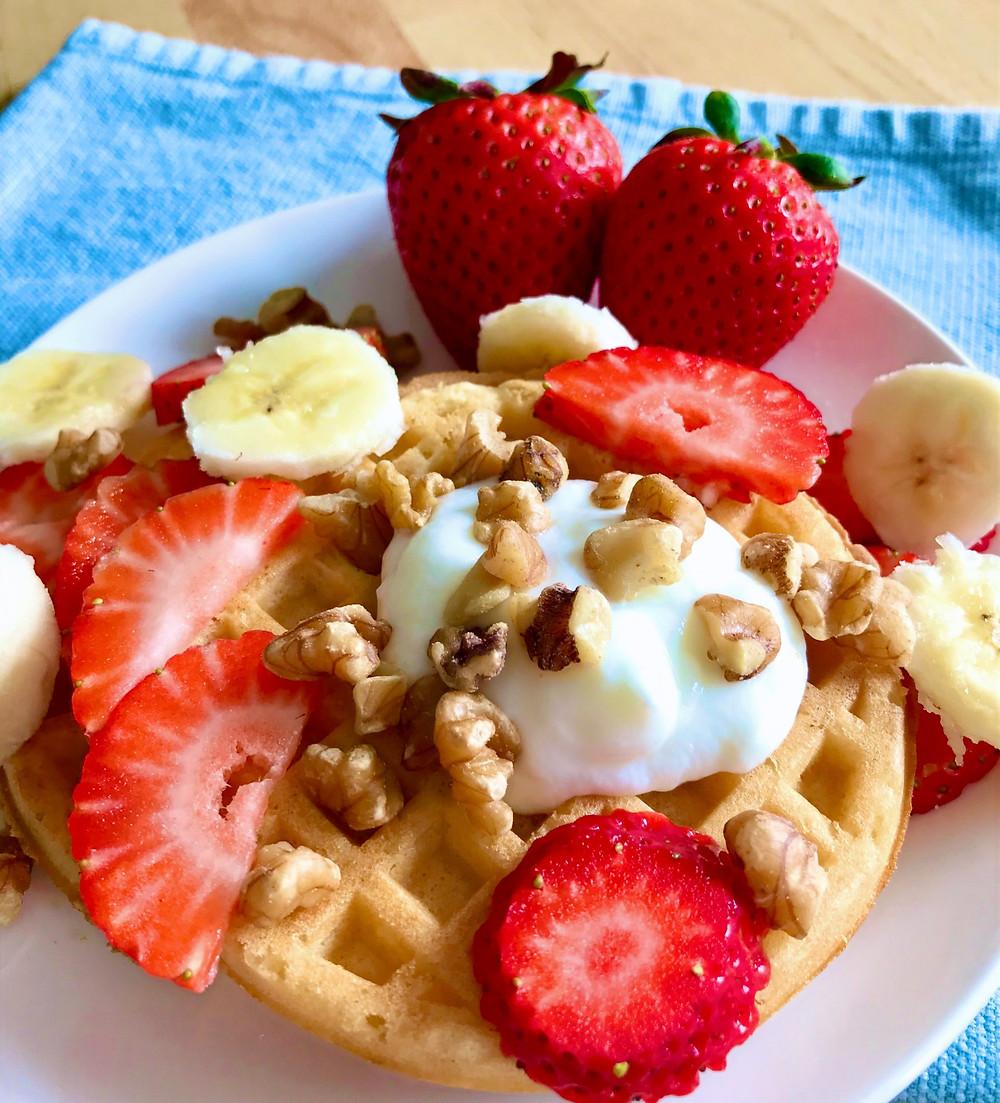 walnut waffles with yogurt, strawberries, and bananas.