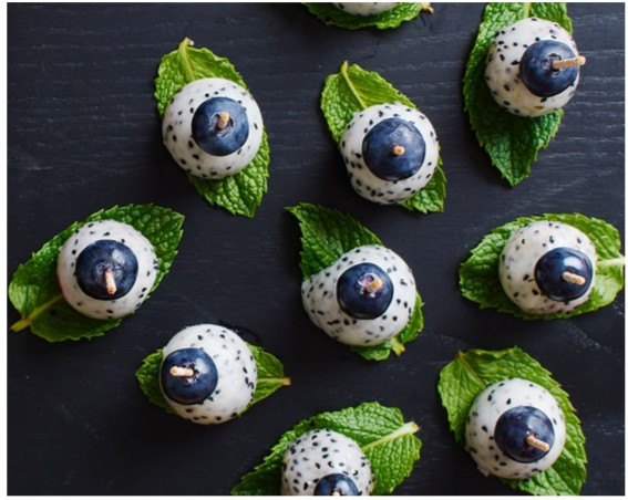 blueberries attached to dragonfruit on top of mint leaves to look like eyes