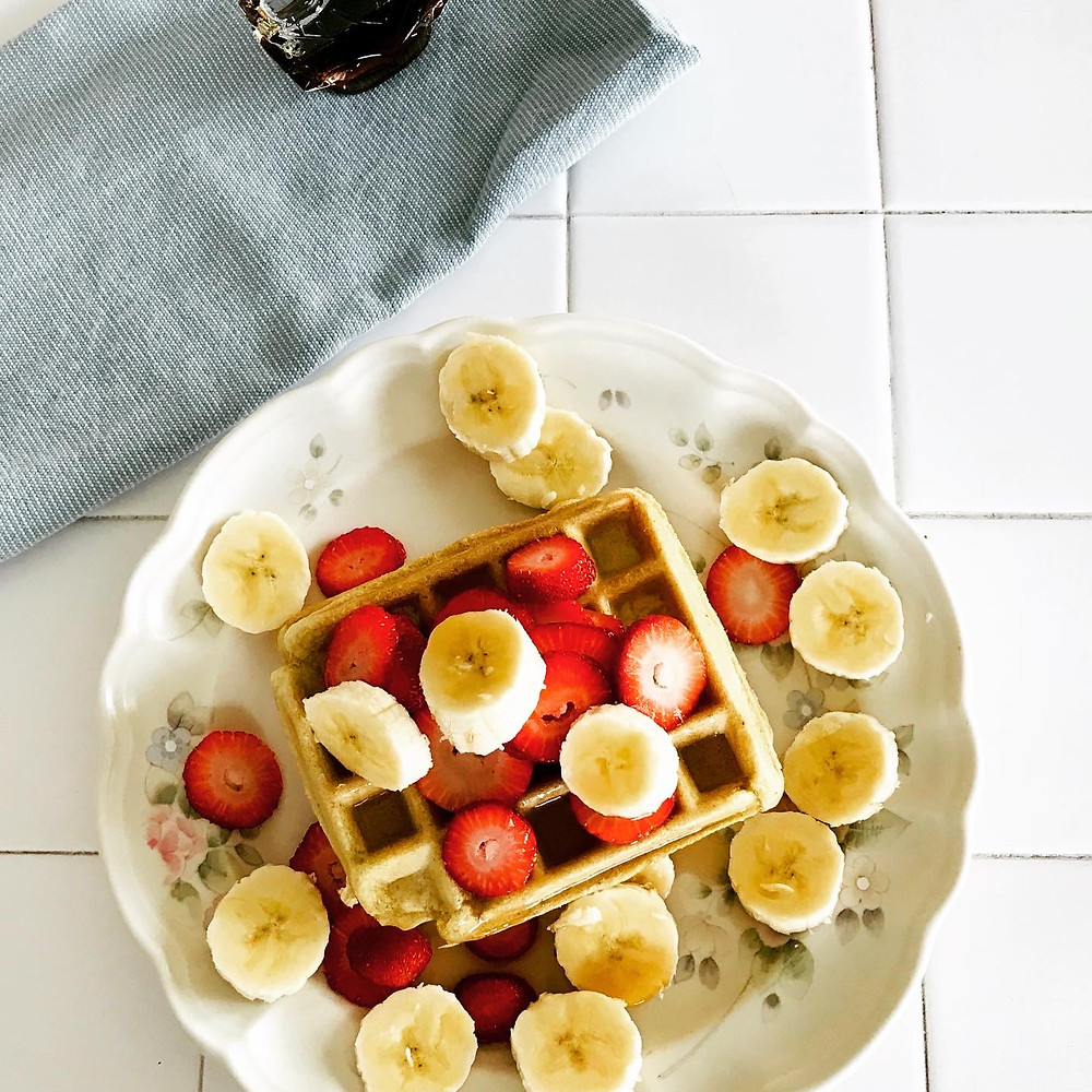 maple syrup, banana, gluten free pumpkin waffle with banana slices on a plate