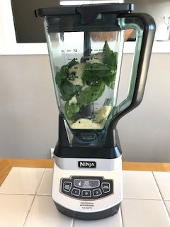 Blender with basil, nuts, and cheese in it