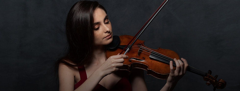 Esther Abrami wearing red dress while playing the violin