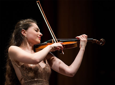 Esther Abrami in gold dress playing the violin during a concert