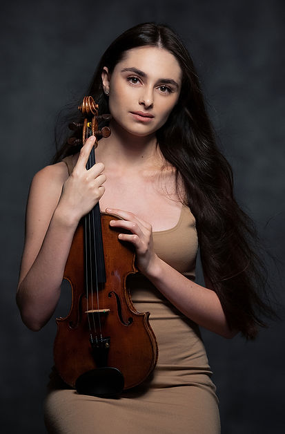 Esther Abrami wearing light brown dress while holding violin