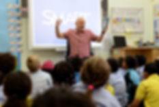 Nick Toczek performing his poetry in a school, 2017.