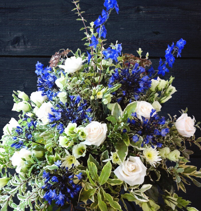 stunning bold bright flower arrangement for a wedding by buds to bouquets delphinium blue and roses