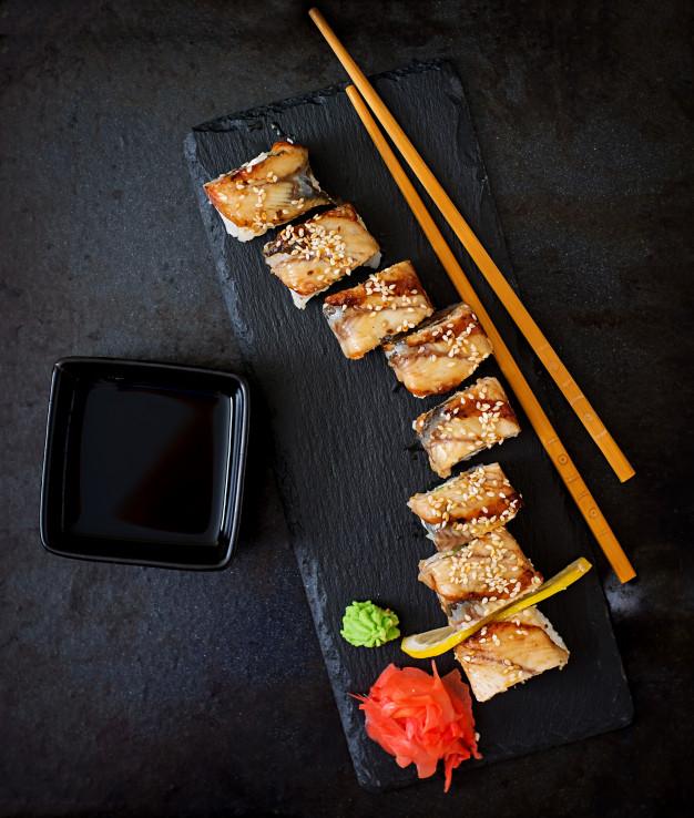 comida-japonesa-tradicional-sushi-rodillos-y-salsa-en-un-fondo-negro_2829-378
