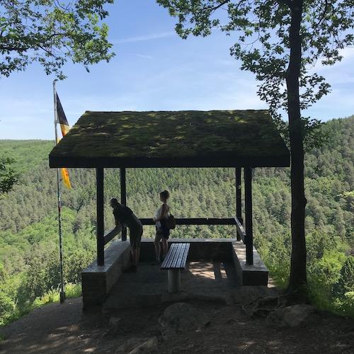 Blotti entre deux chênes, le toit couvert de mousse, un abri ouvert permet d'admirer la vallée du Ninglinspo et le bois de la Picherotte, où feuillus et conifères s'étendent à perte de vue.