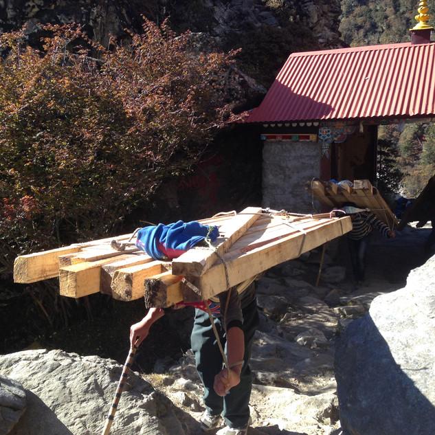 Балки для строящихся вверху домов заносят портеры.