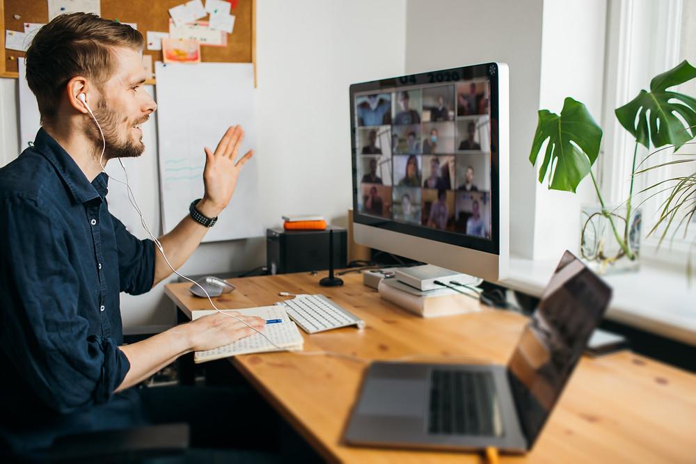 Ein Mann sitzt während einer Videokonferenz vor einem Computer.