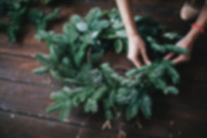 Woman making christmas wreath on a dark