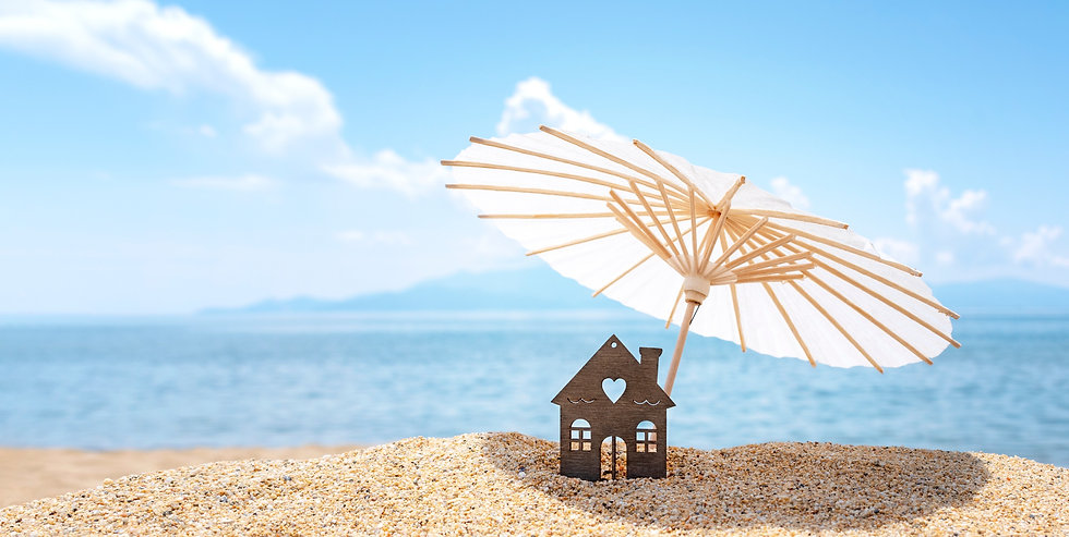 Sun umbrella and house on sandy beach, blue sky and sea in the background. Investment in r