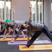 Three beautiful girls and man do yoga in