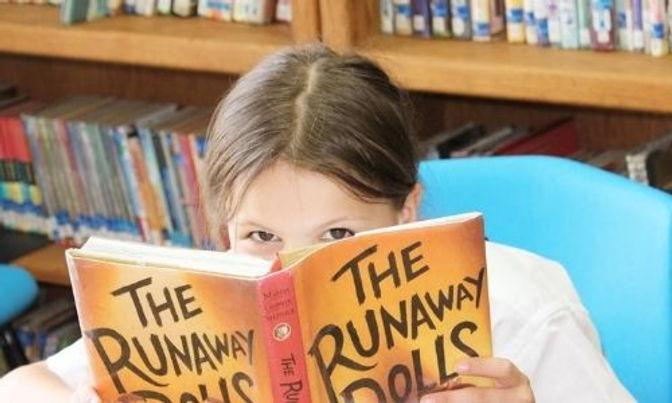 Scofield student peeking over a book she