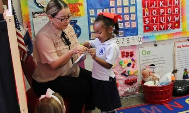 Pre-K teacher with student at Scofield C